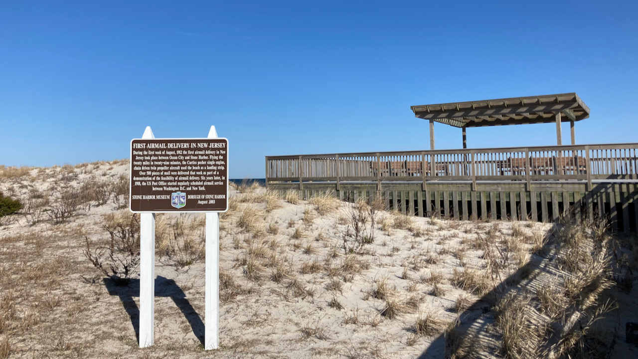 Historical marker on dune near beach.