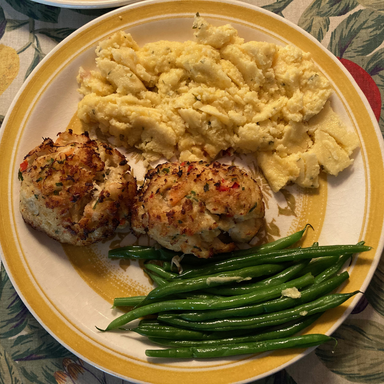 Plate with shrimp and crab cakes, string beans, and polenta.