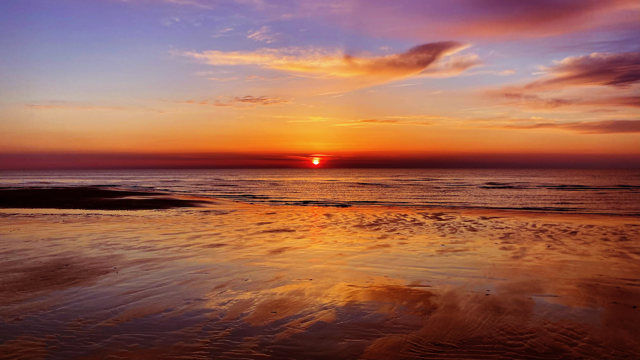 Setting sun over beach, with light reflected in water.