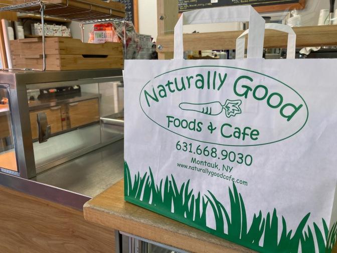 Takeout bag on counter. Bag says NATURALLY GOOD FOOD & CAFE.