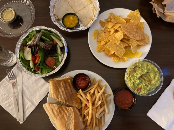 Table with cubano sandwich and fries, another plate with tortilla chips, salad, and quesadilla.