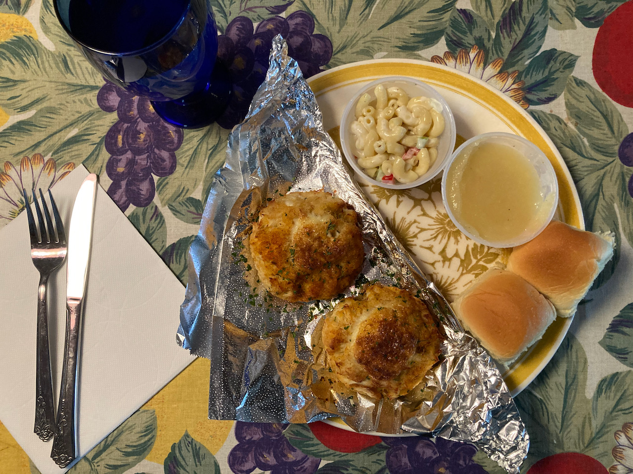 Plate with crab cakes, macaroni salad, and apple sauce.