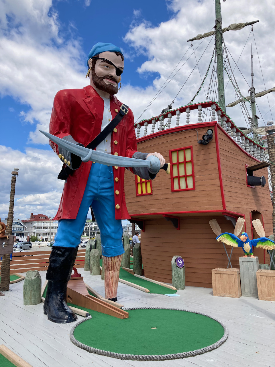 Statue dressed as pirate, standing above miniature gold course hole. A pirate ship is in the background.