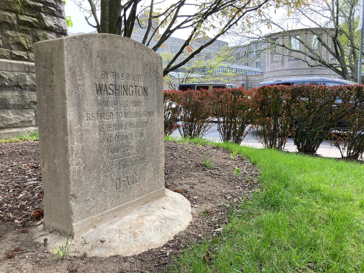 Stone marker beside building that says BY THIS ROUTE WASHINGTON WITH HIS ARMY RETIRED TO MORRISTOWN AFTER HIS VICTORY AT PRINCETON.