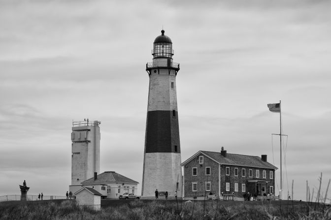 Black and white photo of Montauk Point light and associated buildings.