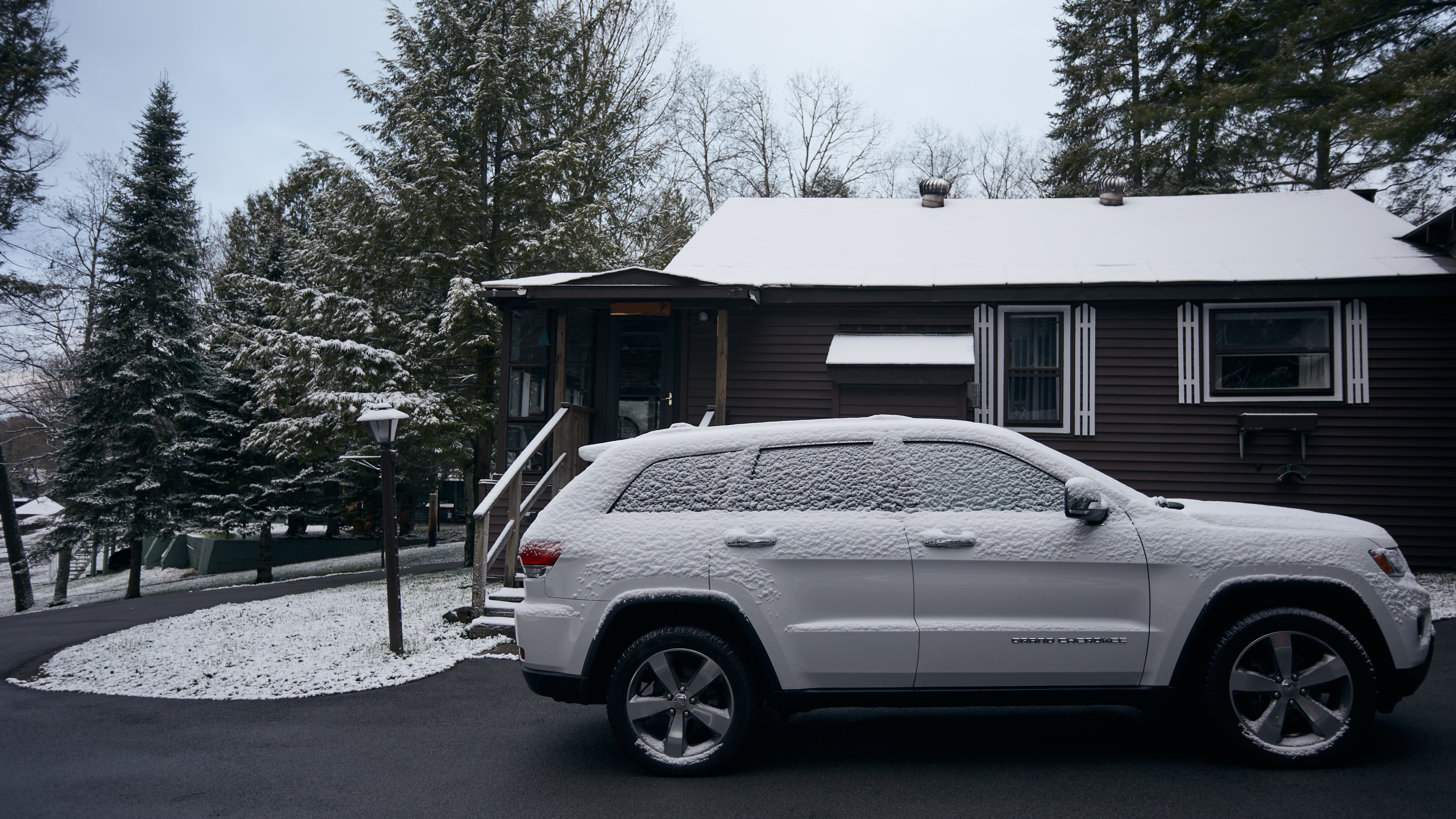 Jeep Grand Cherokee covered in snow, parked in front of house.