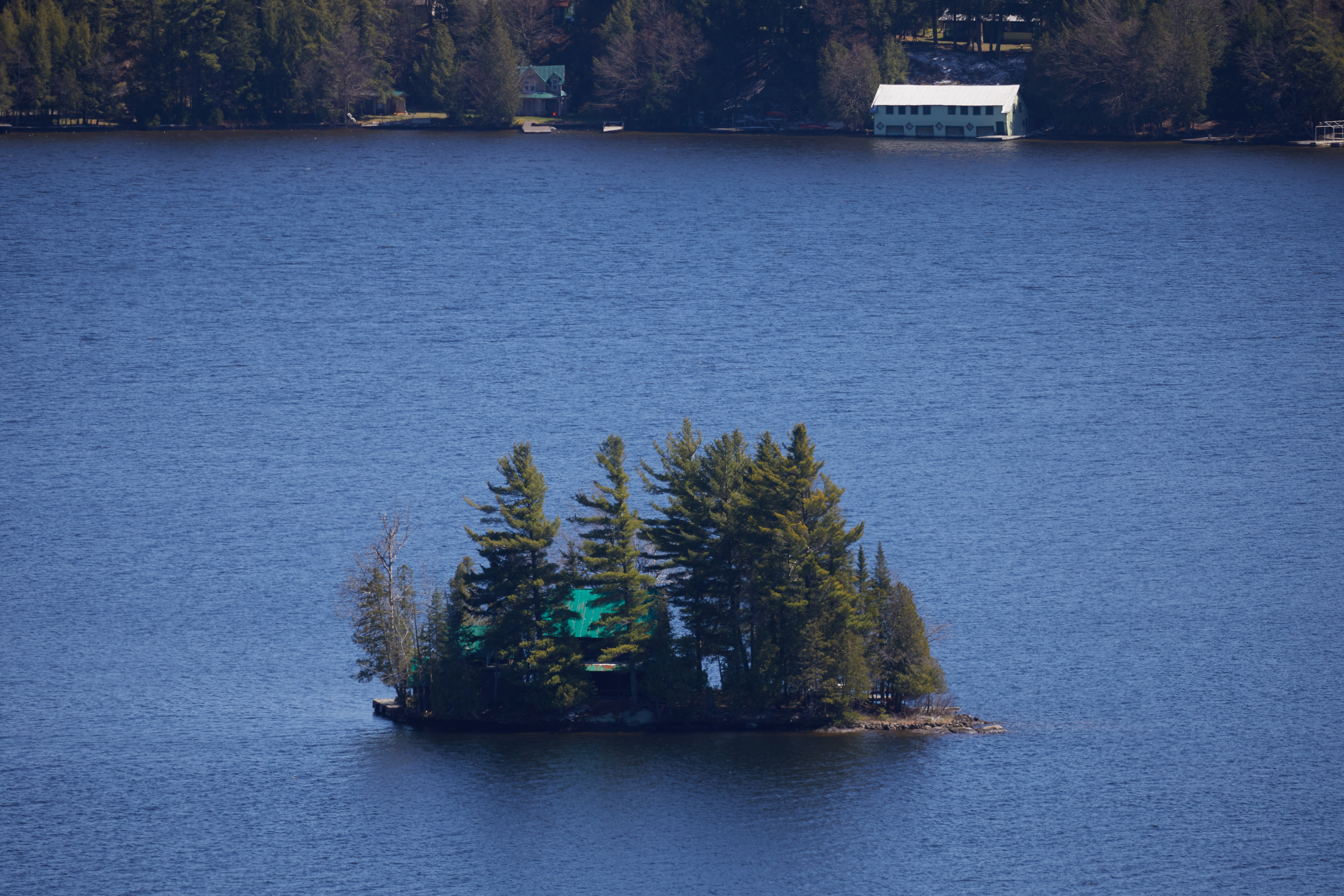 View of small island in lake with house on it.