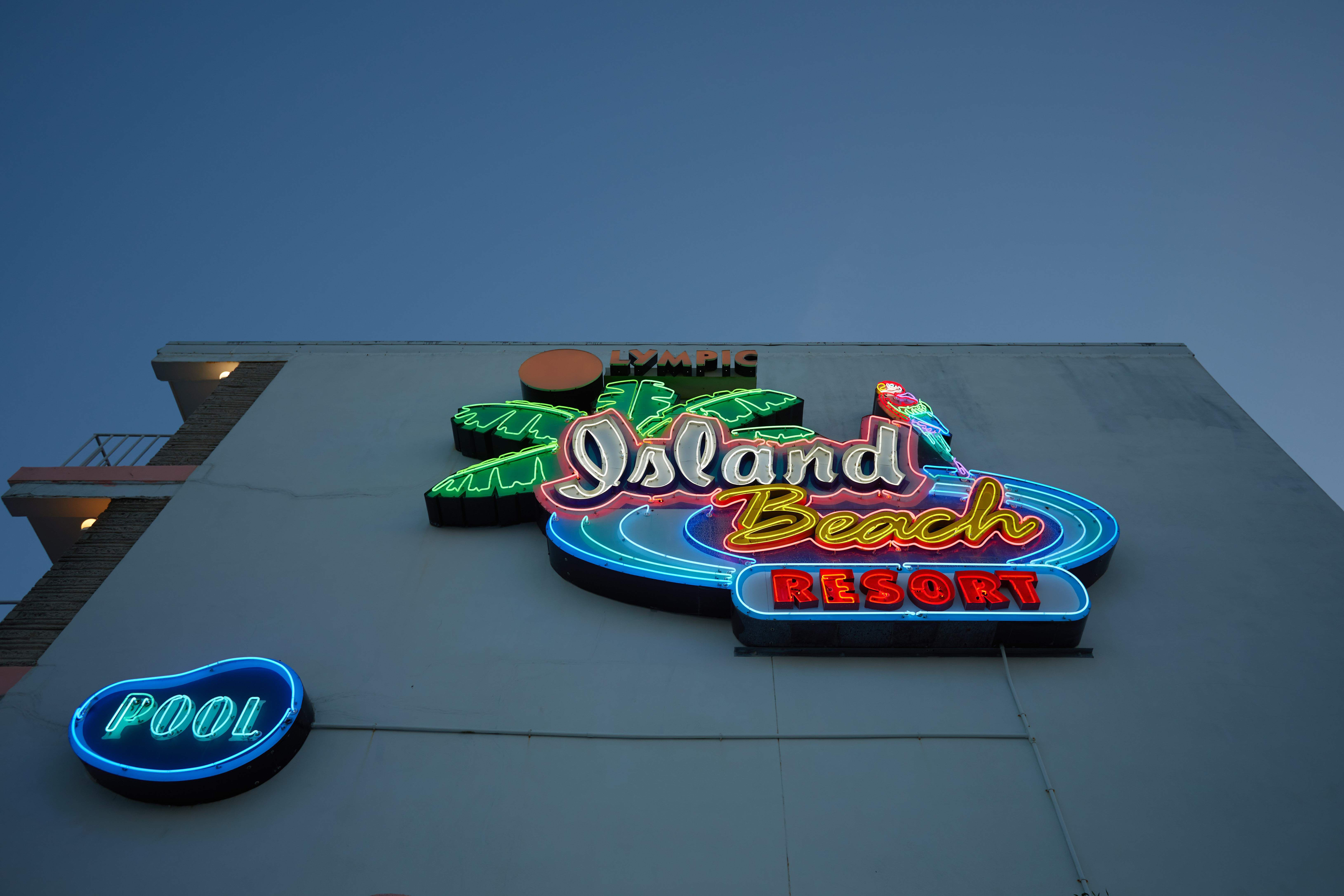 Neon sign on side of building that reads Olympic Island Beach Resort