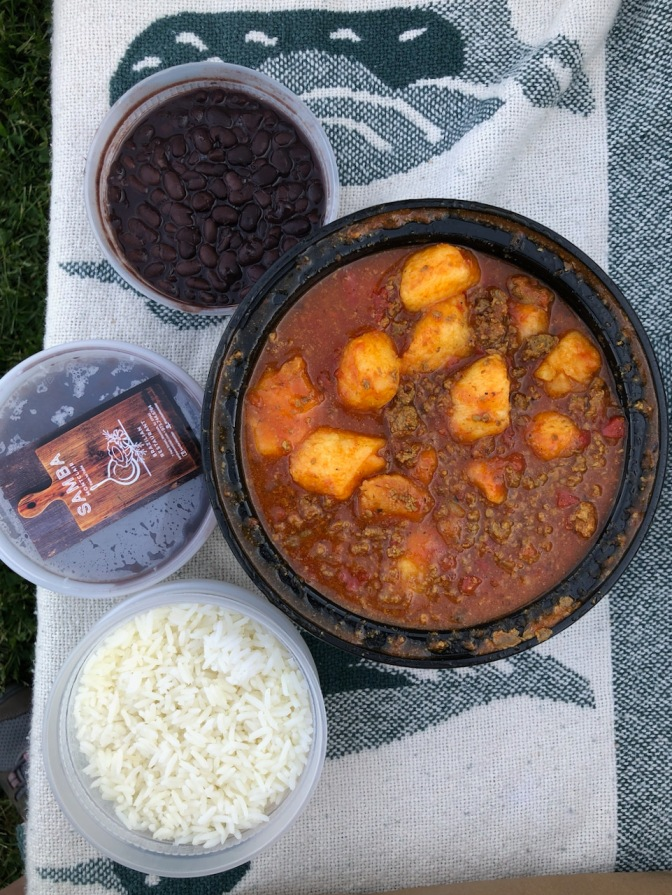 Plastic containers of food - one with white rice, one with black beans, and one with meat gnocchi.
