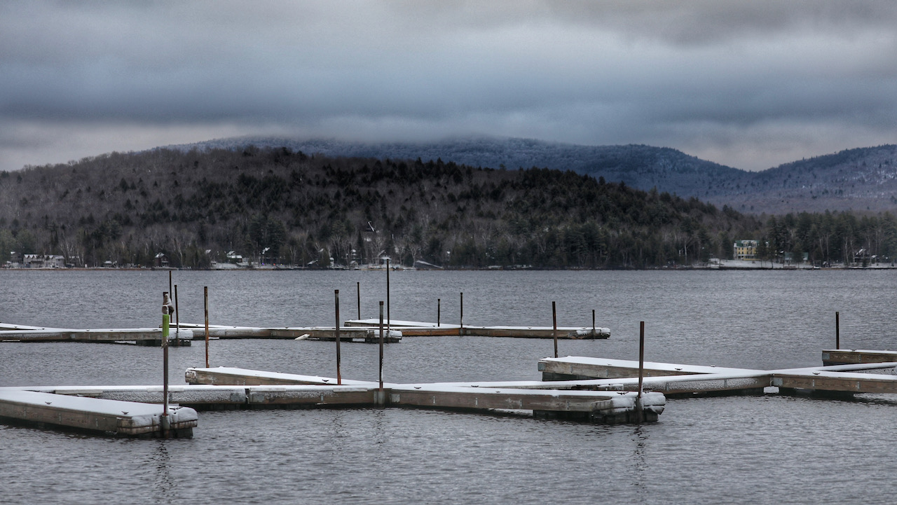 Docks covered in sow, with cloudy mountain in the distance.