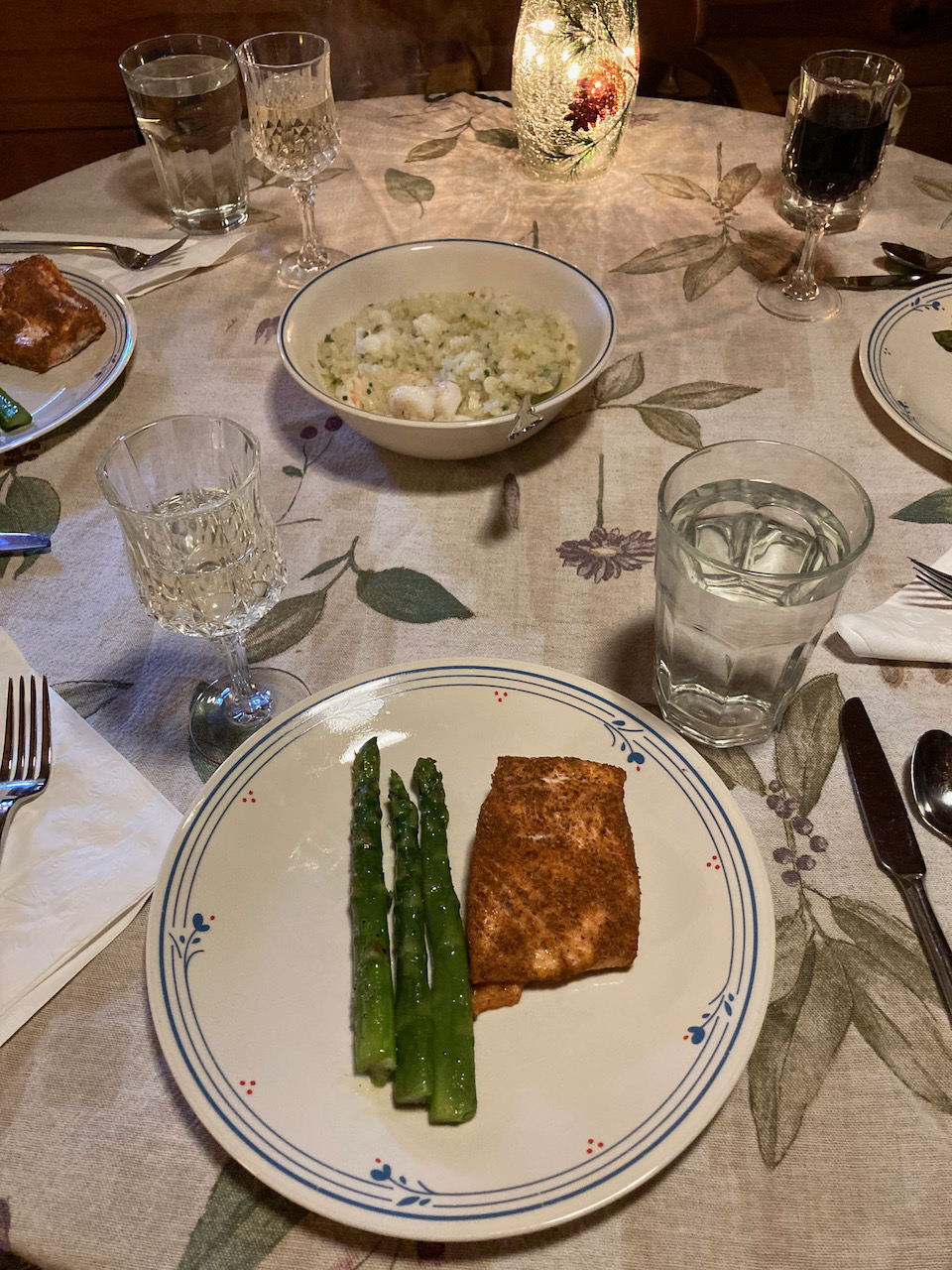 Plates of asparagus, salmon, and seafood risotto.