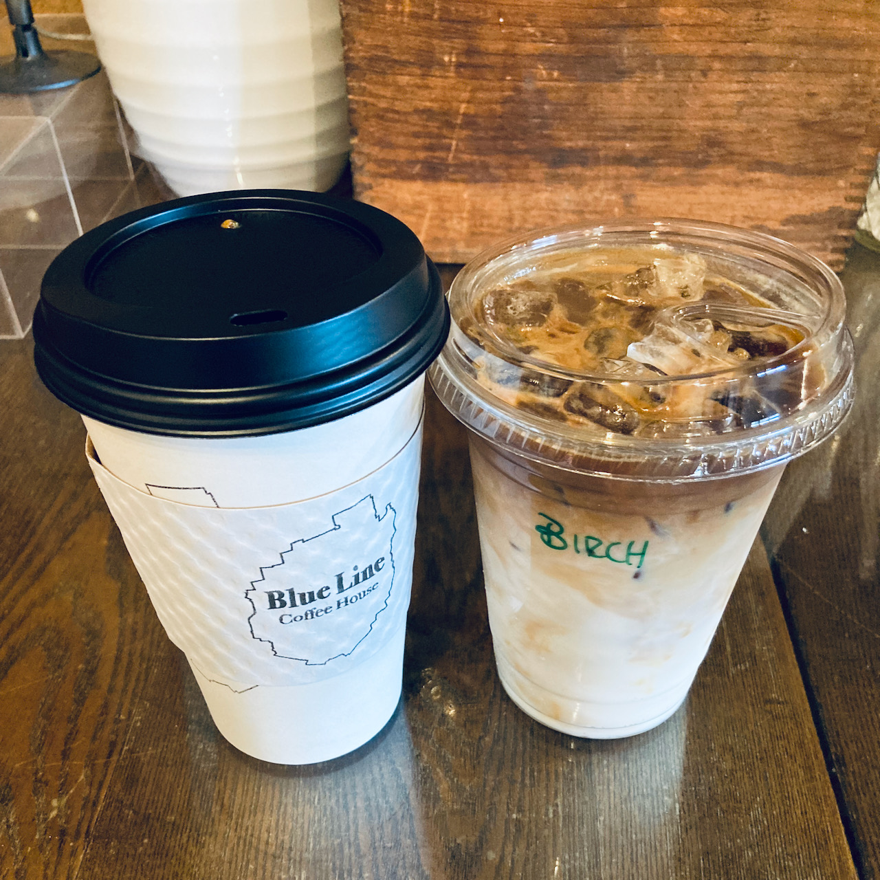 Cup of hot coffee on left and cup of iced coffee on right.
