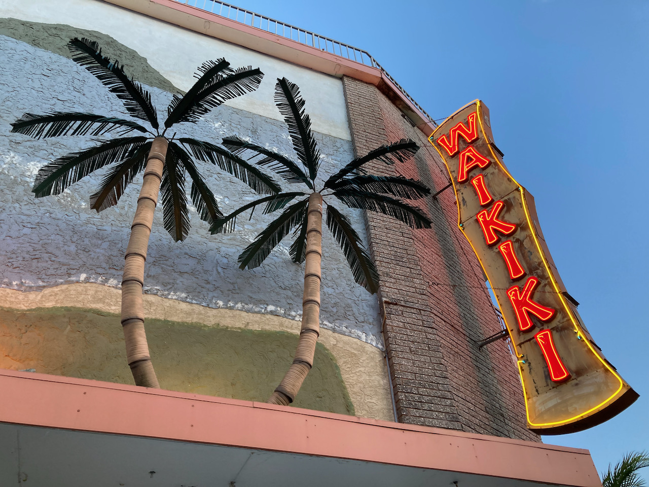Exterior of Waikiki hotel, with two plastic palm trees.