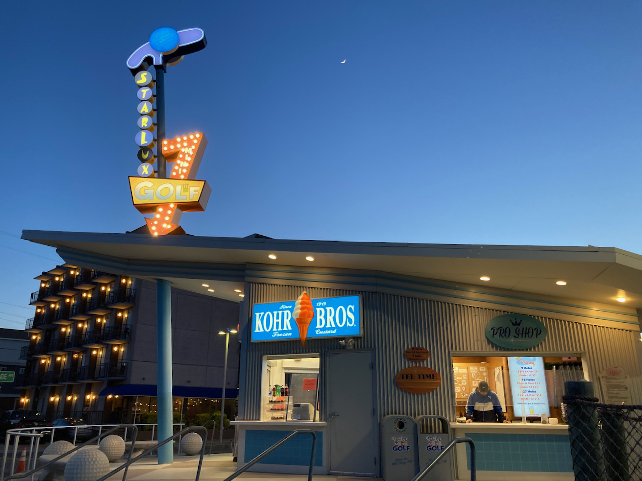 Exterior of Kohr Bros. frozen custard shop, with doo wop style sign for Starlux Golf on top of building.
