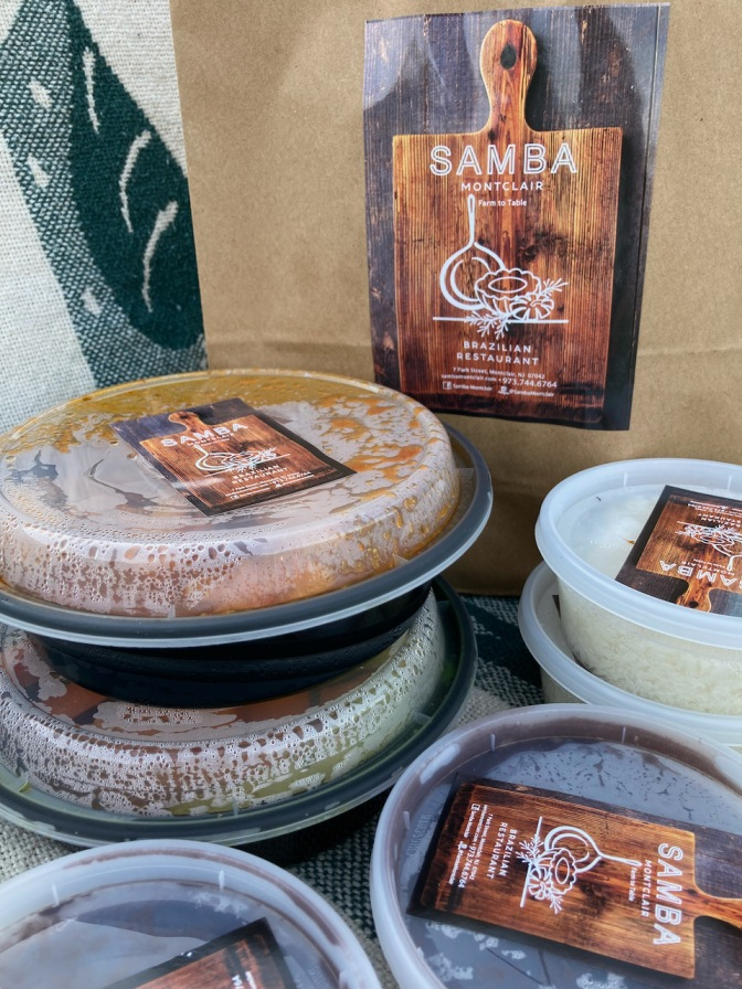 Take-out bag from Samba restaurant, along with several plastic containers of food.