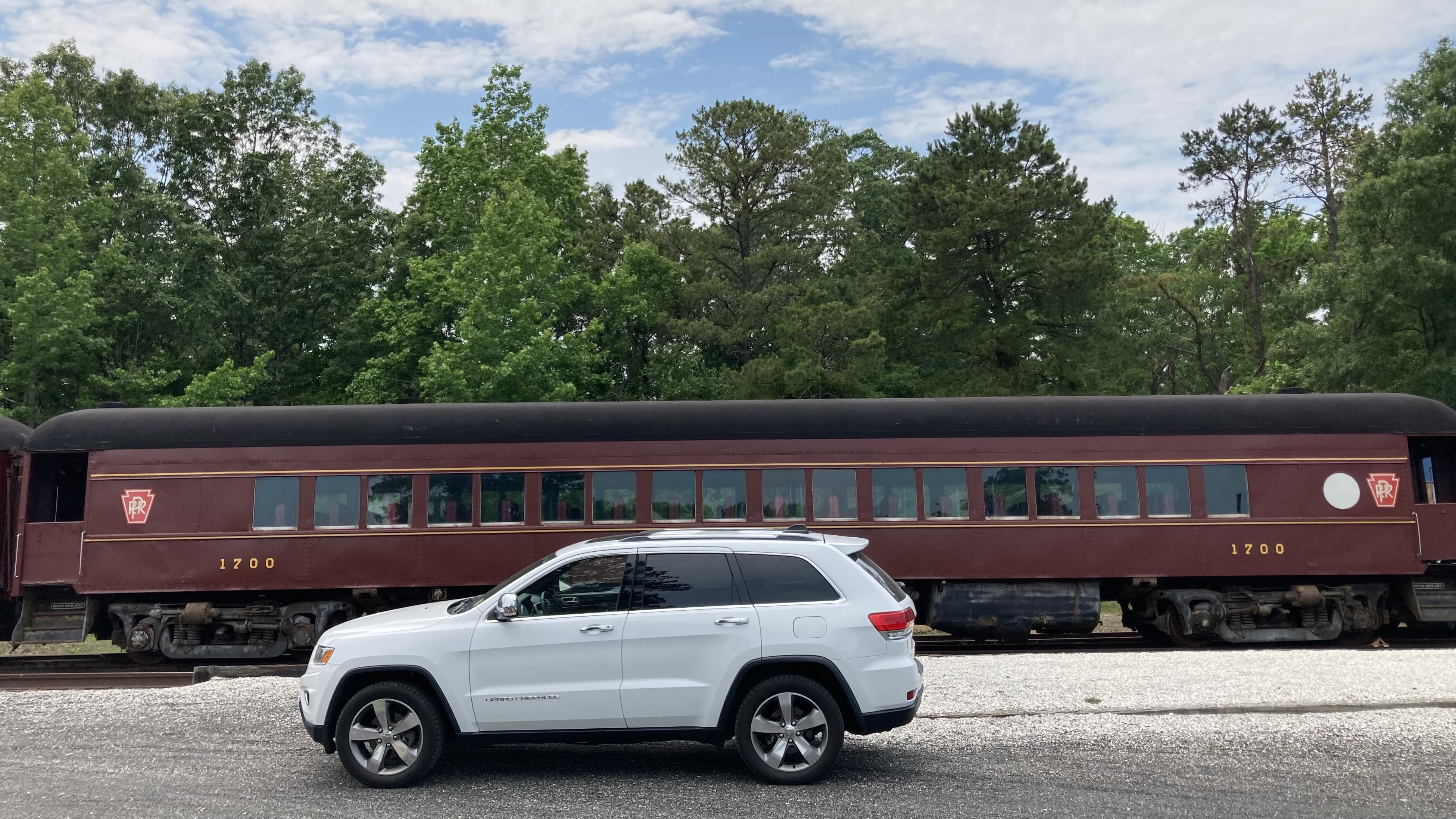 White Jeep Grand Cherokee parked in front of train passenger car in train yard.