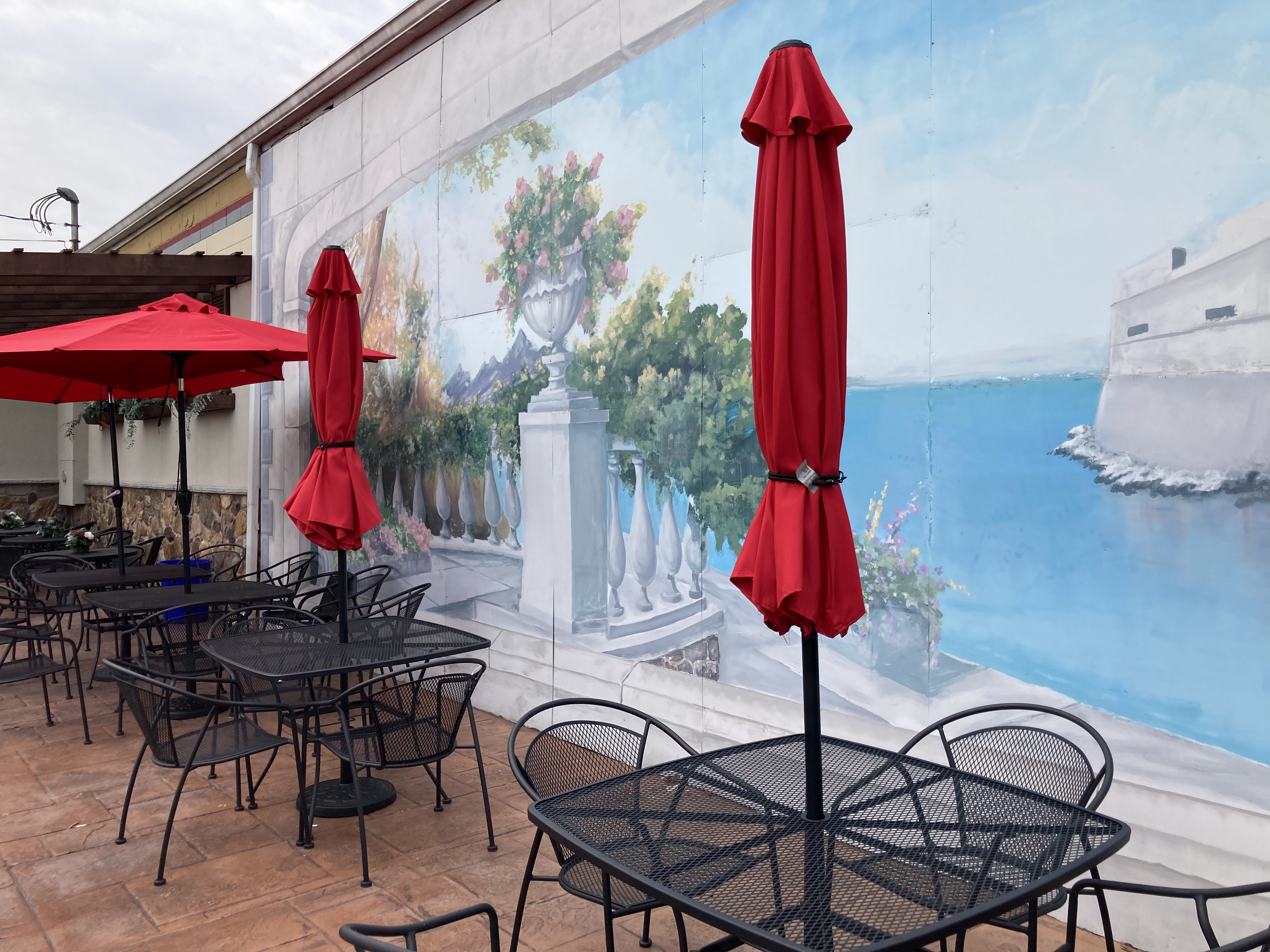 Outdoor patio, with a wall mural on outside of building of a view of the Adriatic Sea.