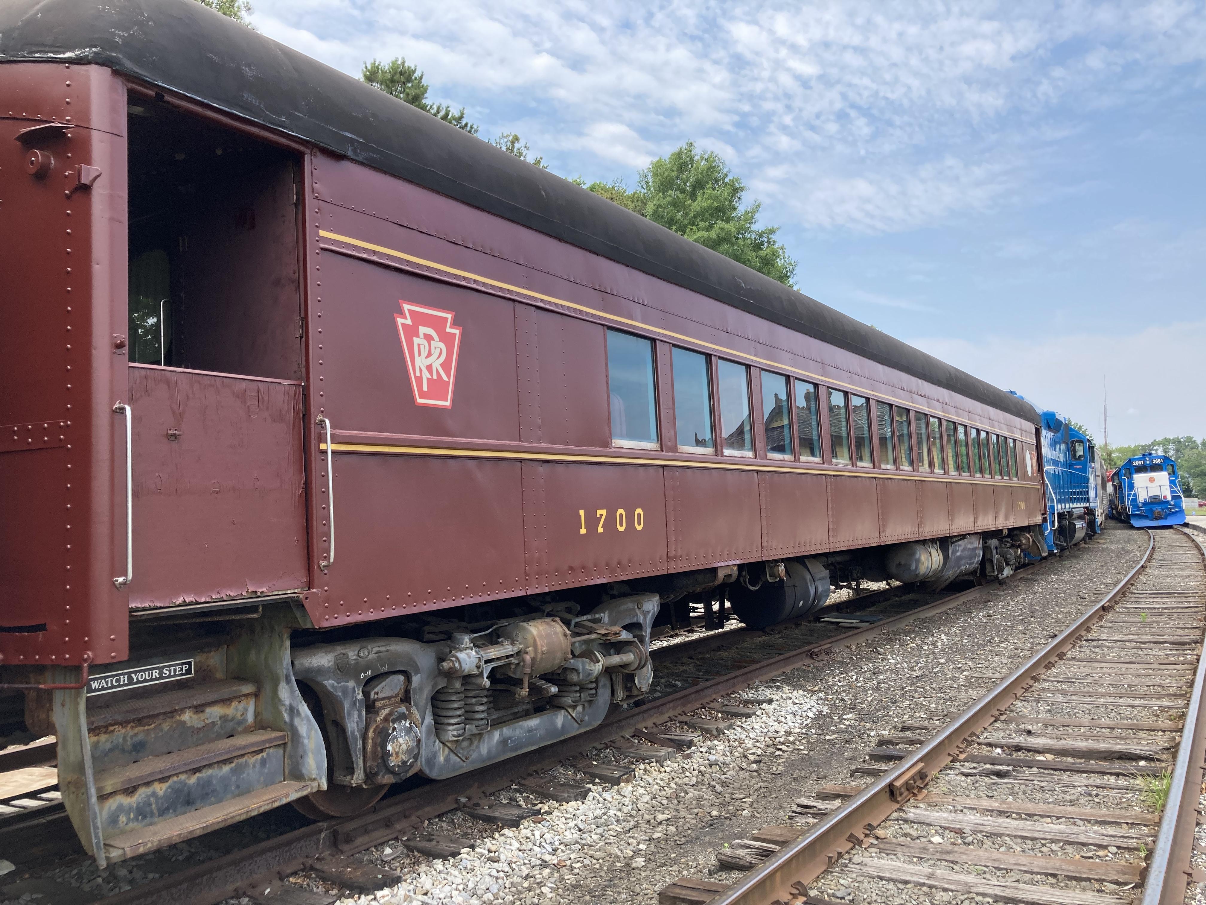 Pennsylvania Rail Road passenger car parked in train yard.