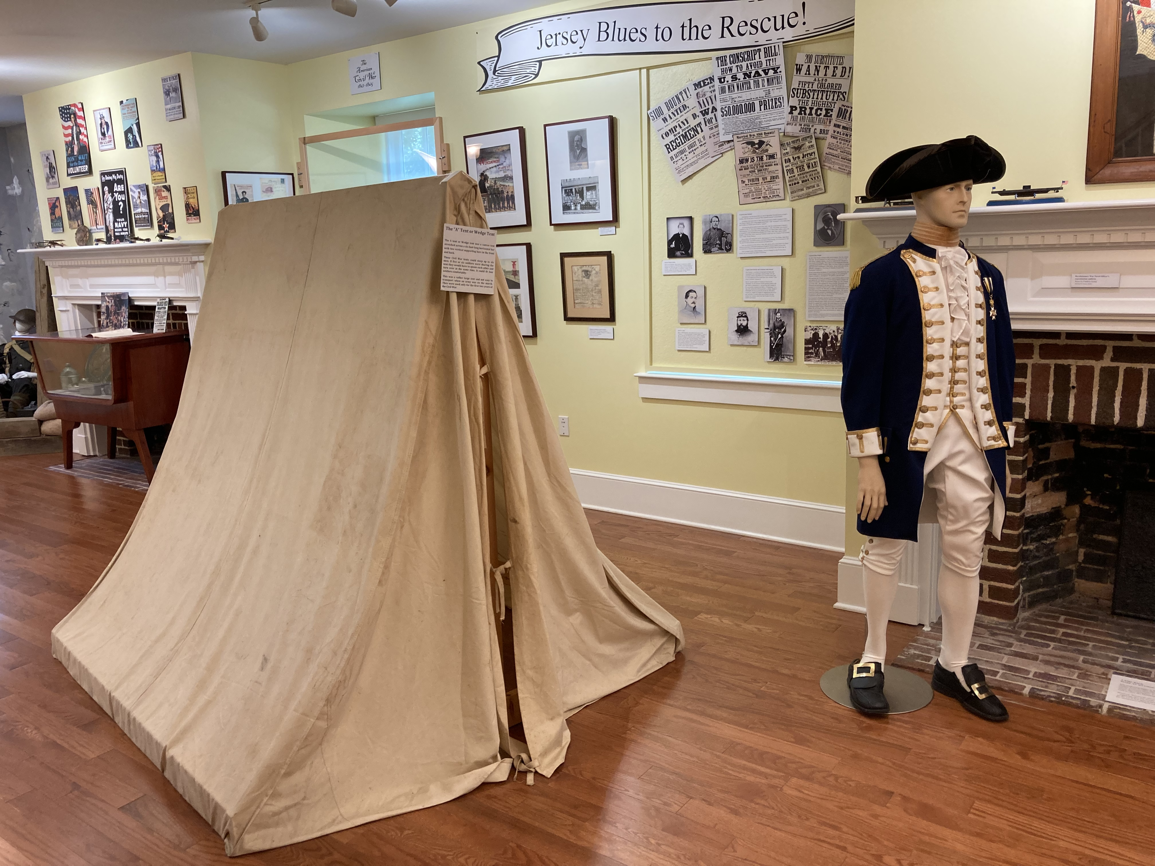 Room with mannequin dressed in Revolutionary War attire, and a small soldier's tent.