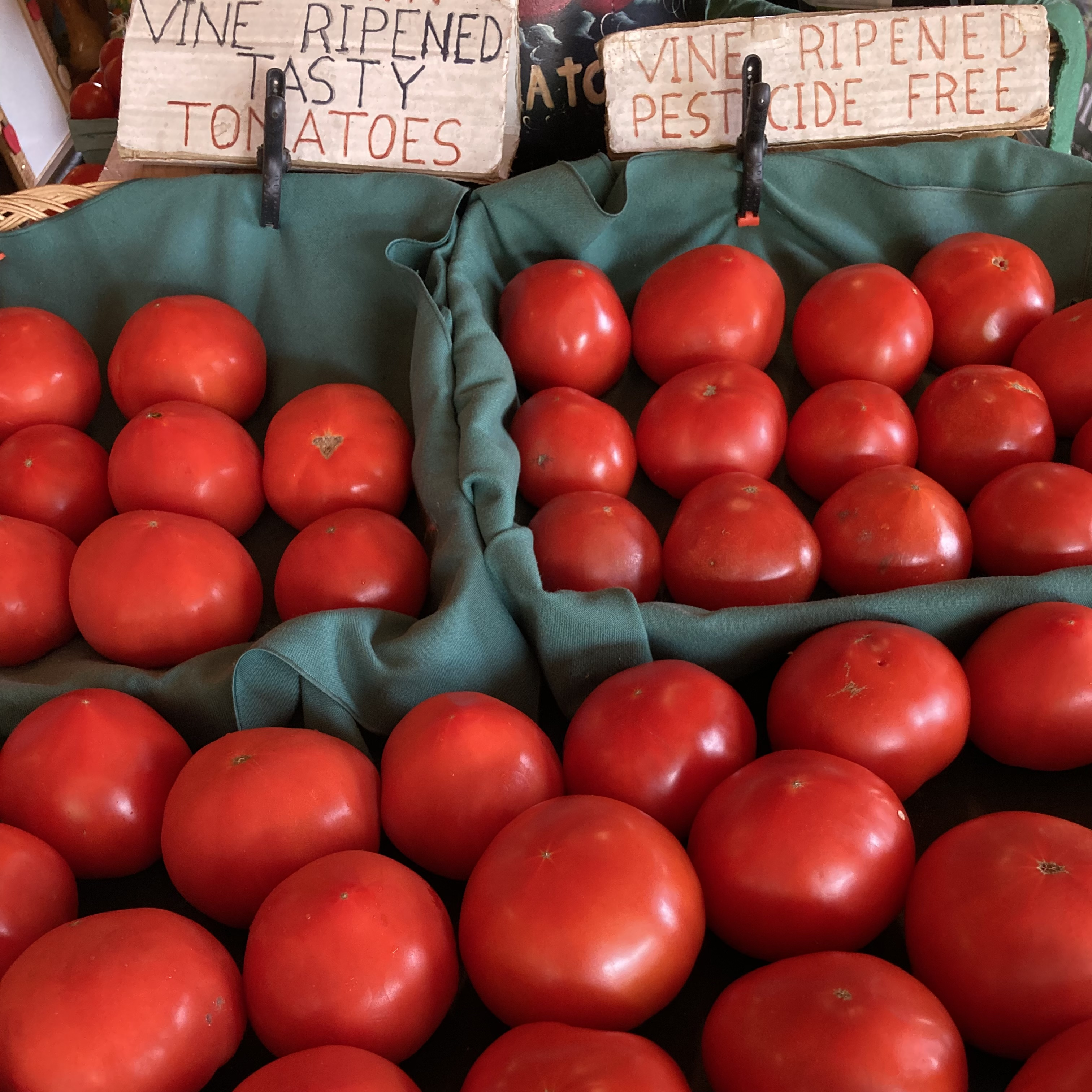 Stand of red tomatoes, with sign that says VINE RIPENED TASTY TOMATOES