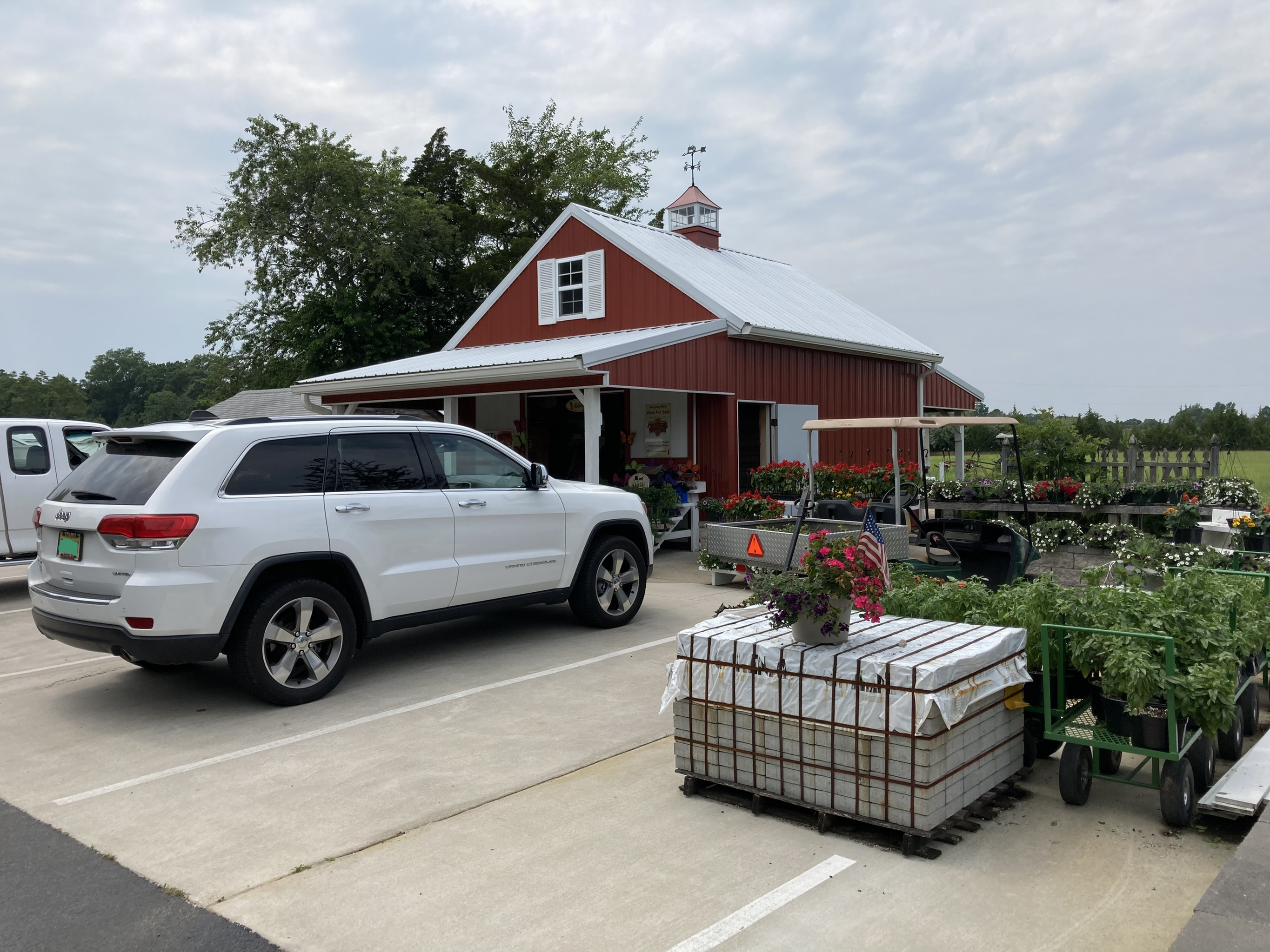 White Jeep Grand Cherokee, parked in front of farm stand.