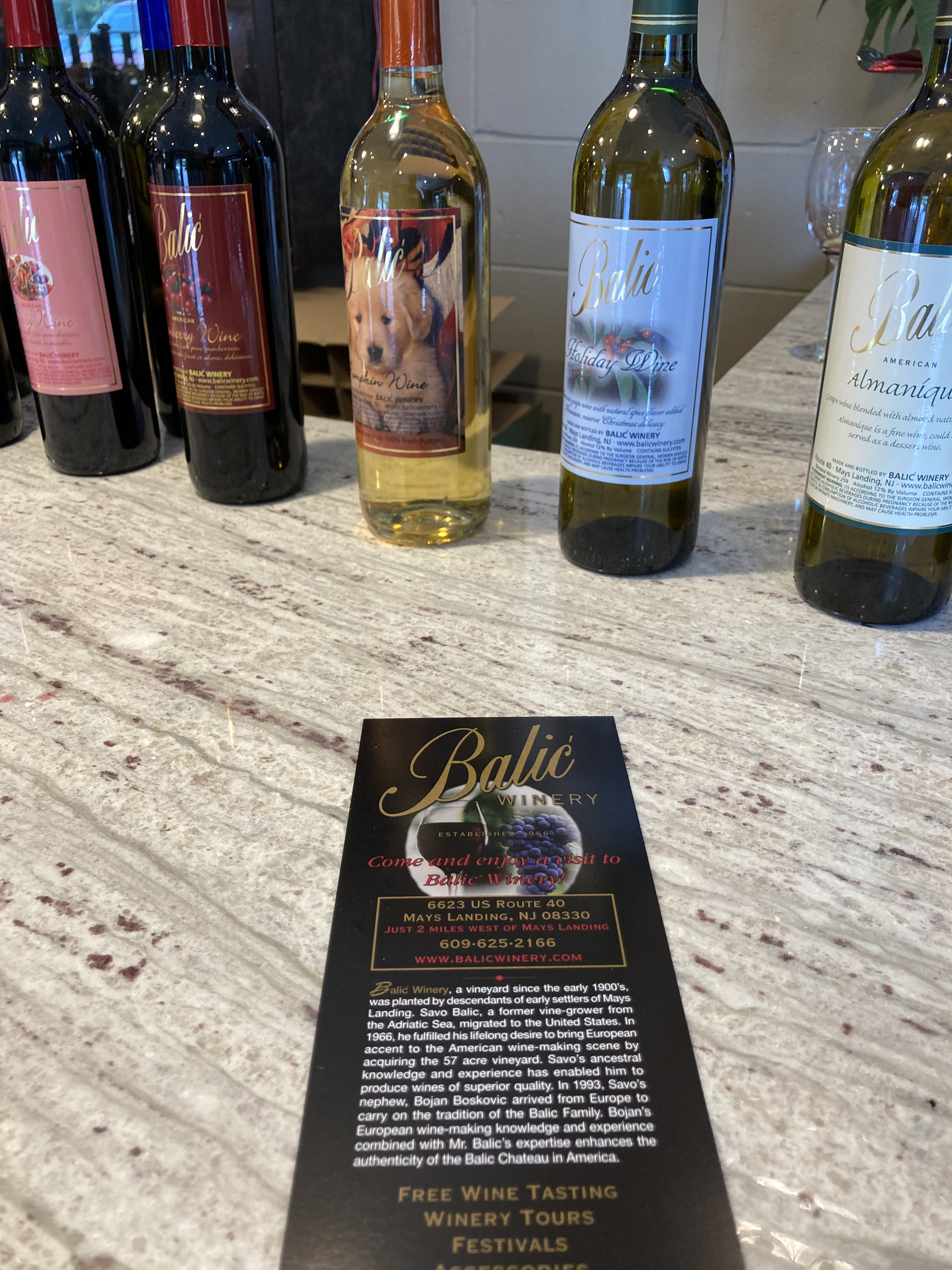 Wine bottles on counter, with small menu in foreground.