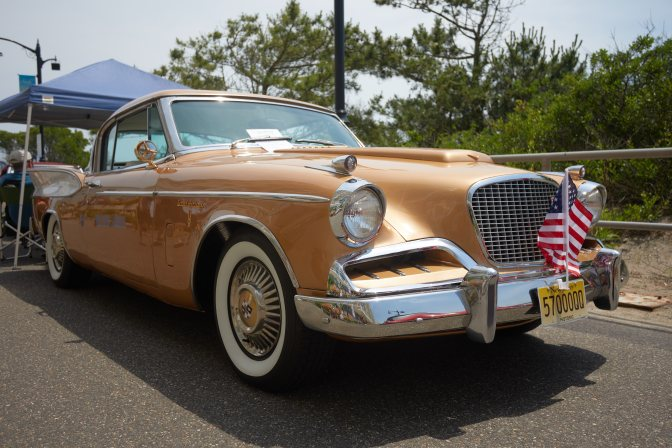 Gold Studebaker coupe parked on promenade.
