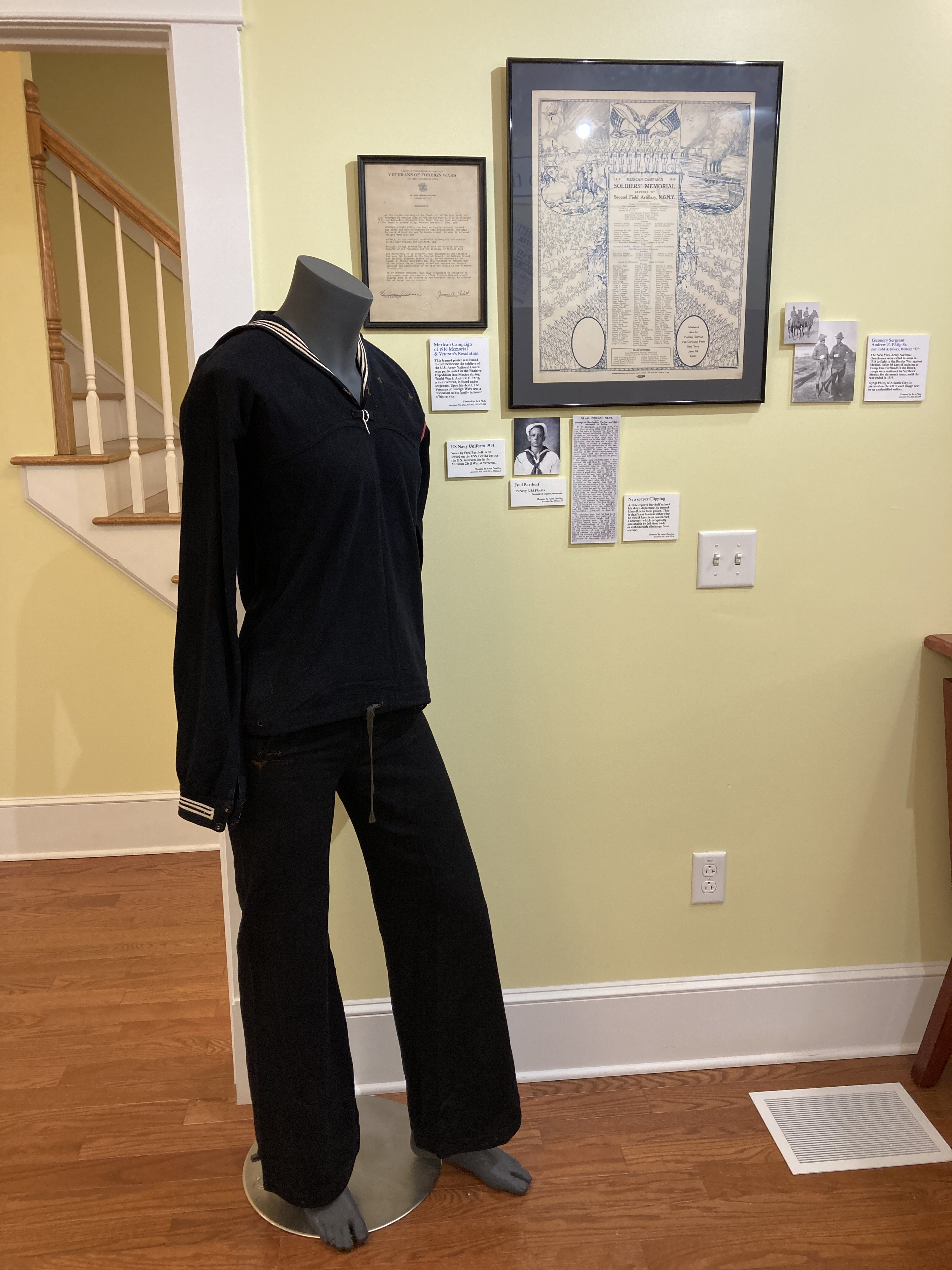 1914 US Navy uniform on mannequin, with wall display of documents behind it.