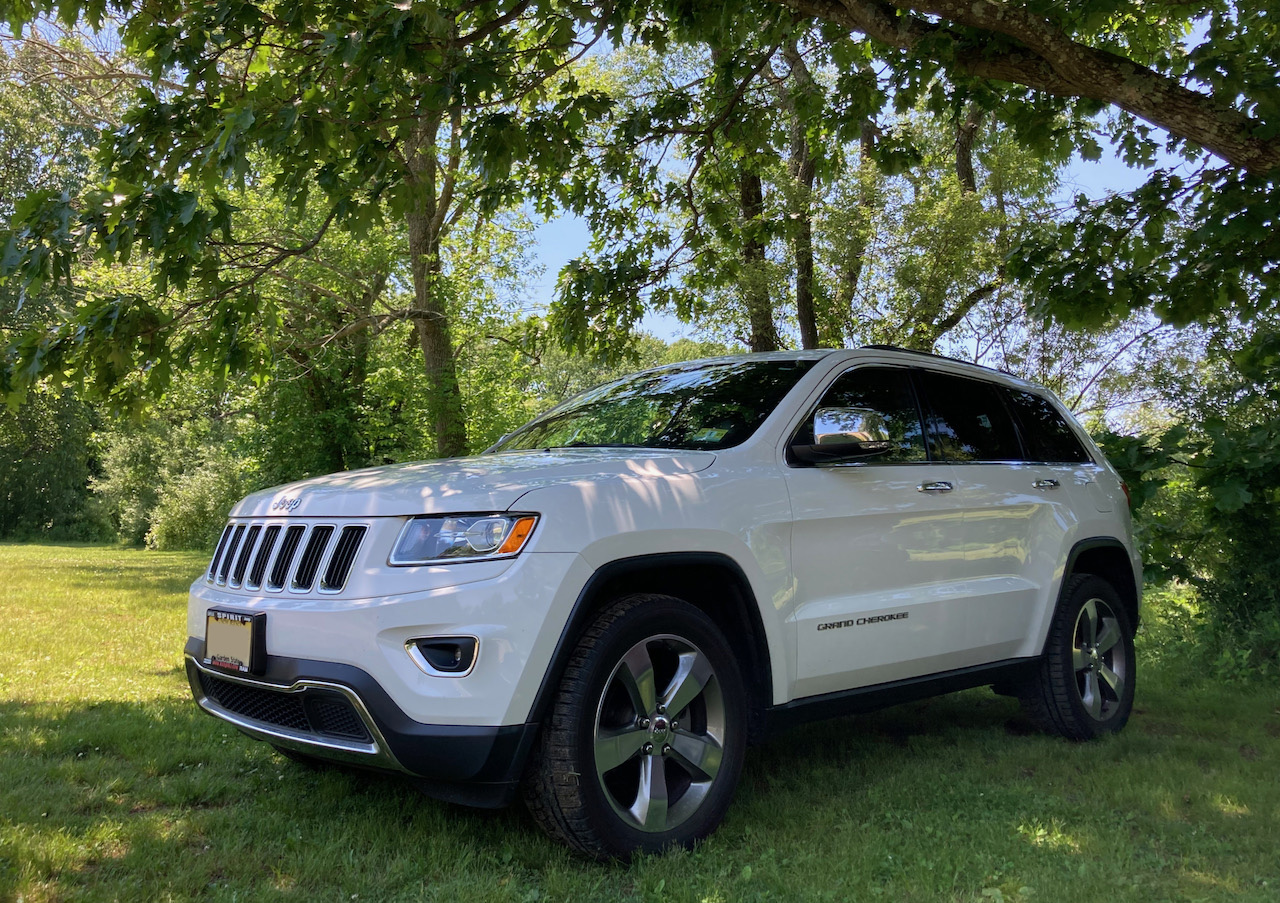 White Jeep Grand Cherokee, parked on grass beneath a tree.