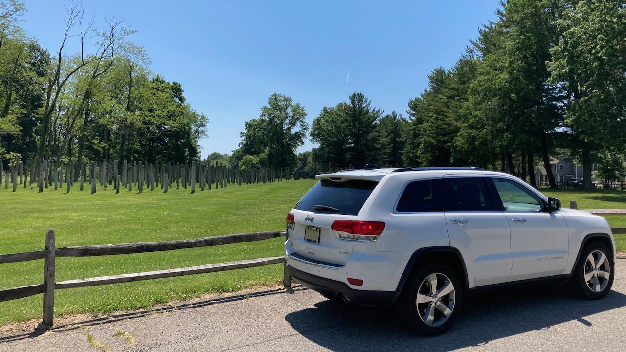 White Jeep Grand Cherokee parked beside Telephone Pole Farm.