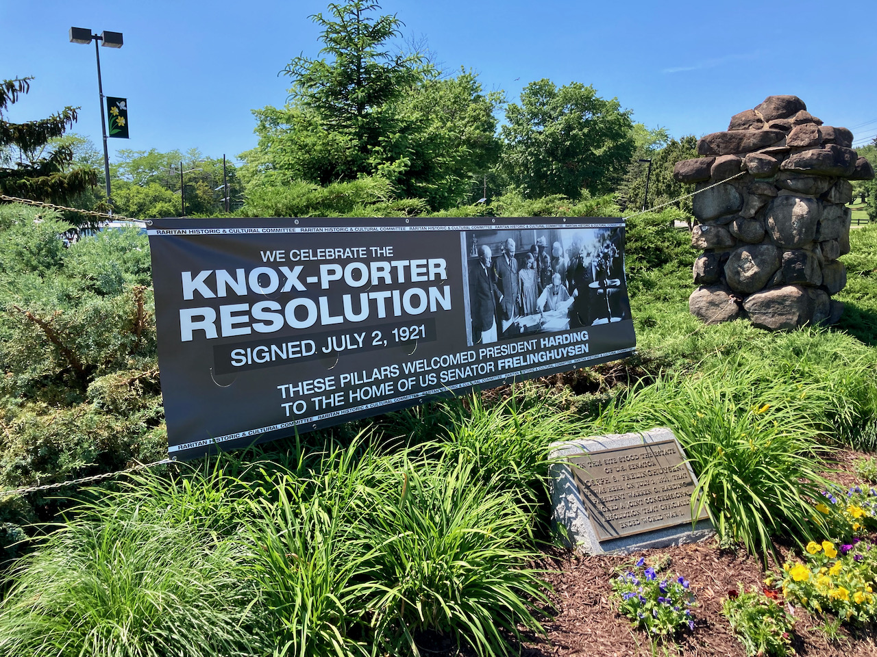 Small stone marker with plaque amid shrubbery. A large sign is hanging in the background, that states WE CELEBRATE THE KNOX-PORTER RESOLUTION SIGNED JULY 2, 1921 - THESE PILLARES WELCOMES PRESIDENT HARDING TO TEH HOME OF US SENATOR FRELINGHUYSEN.