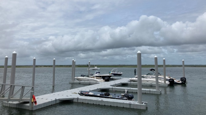 View of bay with dock and boats in foreground.