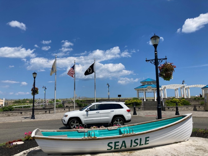 Jeep Grand Cherokee parked in front of row boat that says SEA ISLE on side.