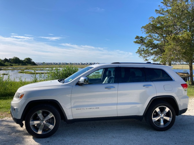 2014 Jeep Grand Cherokee parked in front of wetlands.