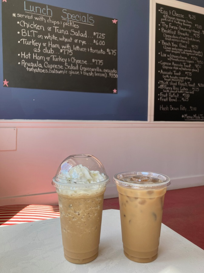Two iced coffees on table, with blackboard on wall in background with lunch specials.