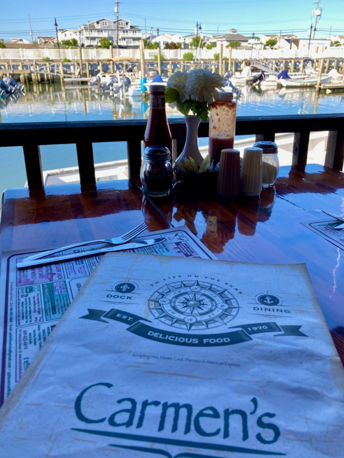 Table with menu for Carmen's, and boats docked in the harbor in the background.