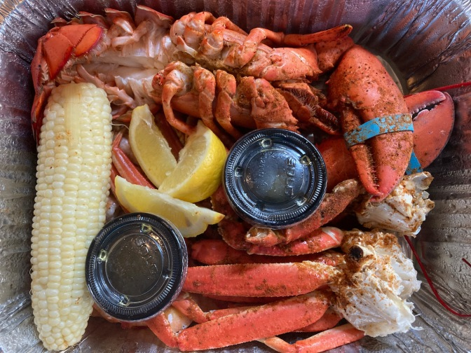 Platter with corn, crab legs, shrimp, and lobster.