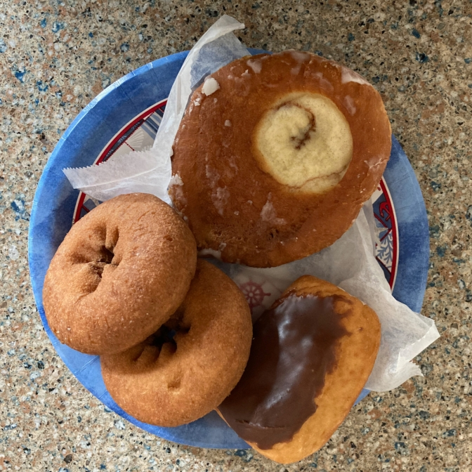 Donut assortment on paper plate.