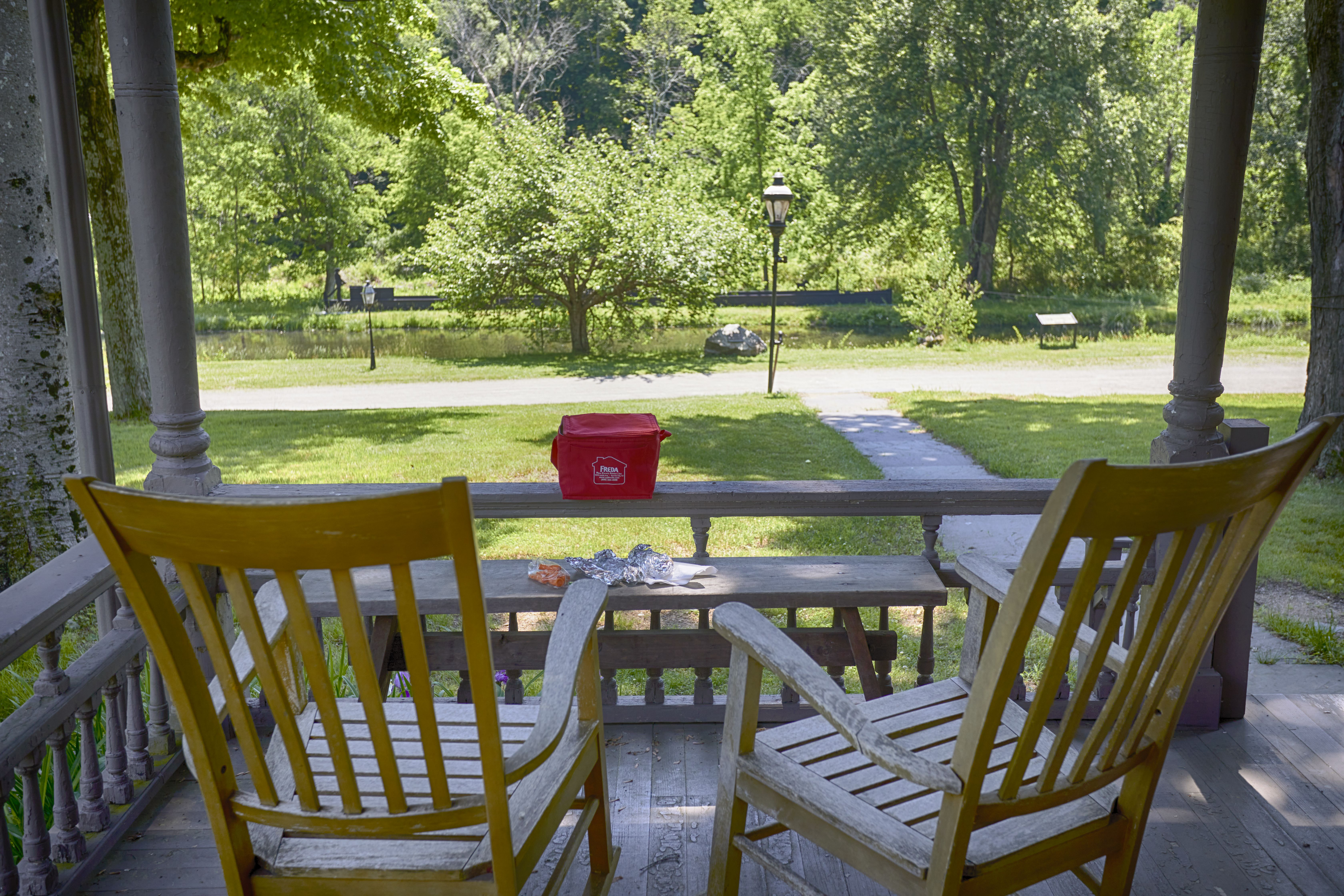 Two rocking chairs on porch, with picnic lunch on small table.