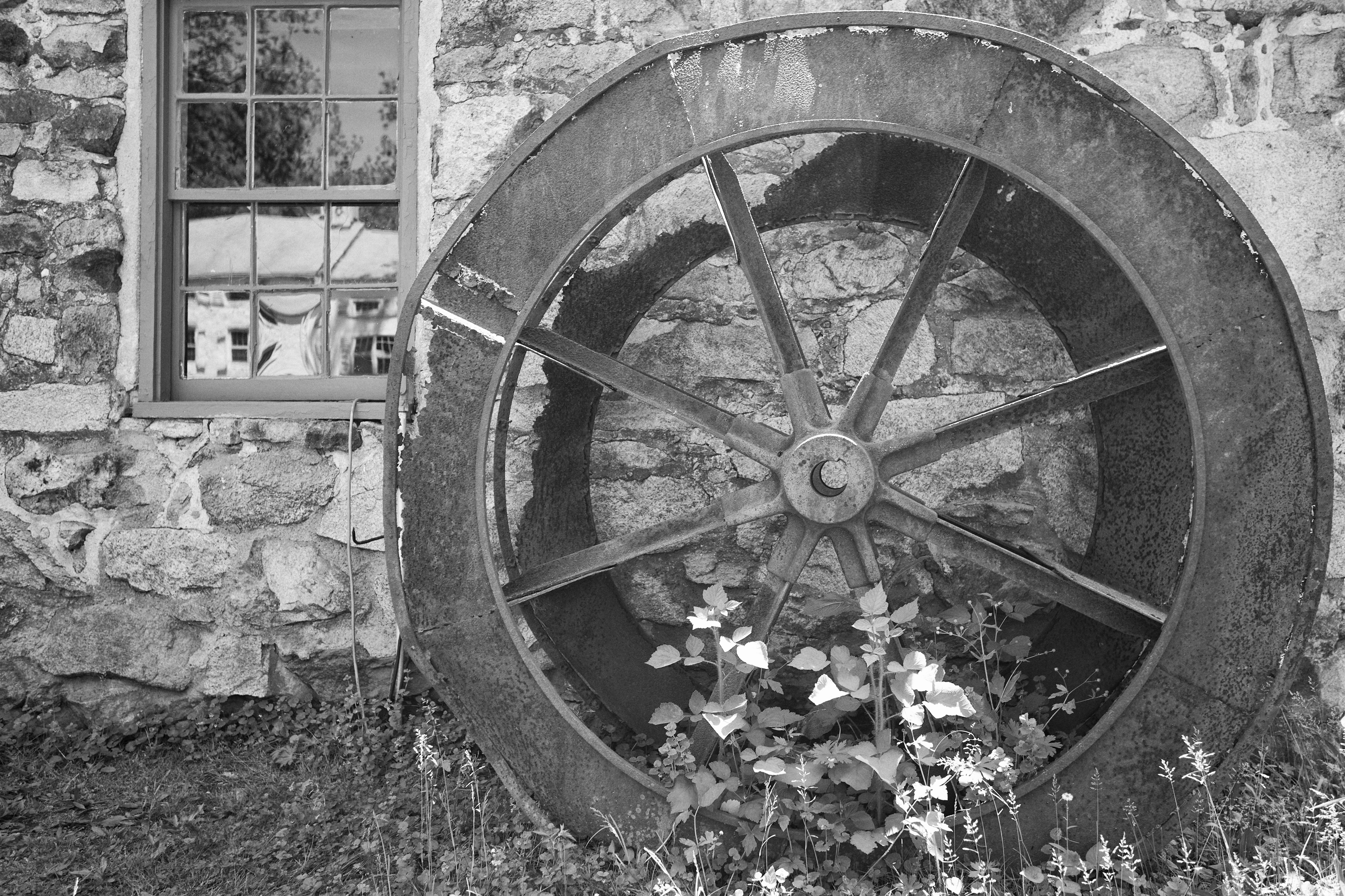 Black and white photo of water wheel beside building.