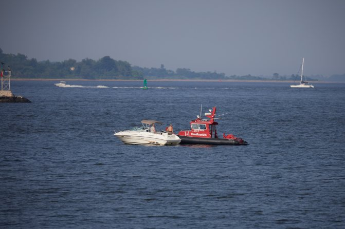 Tow boat coming to assist stricken motor boat.