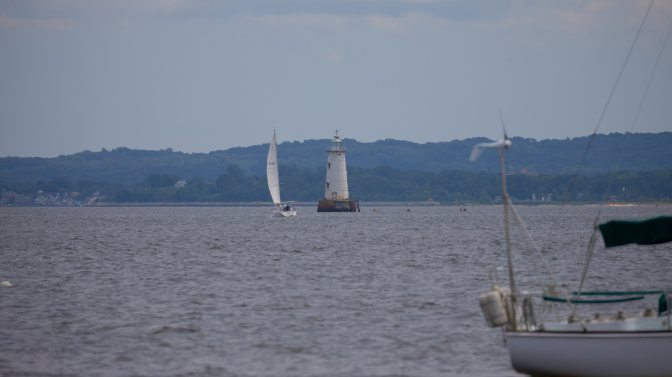 Great Bed Lighthouse with sailboat passing by it in bay.