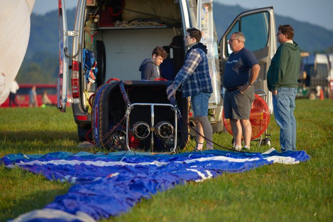 Group of people beginning assembly of hot air balloon, including preparing basket and burners.