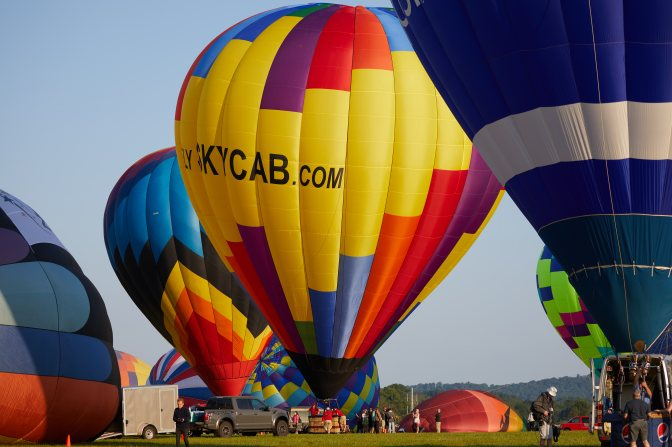 Three balloons, inflated, on ground, and preparing to fly.
