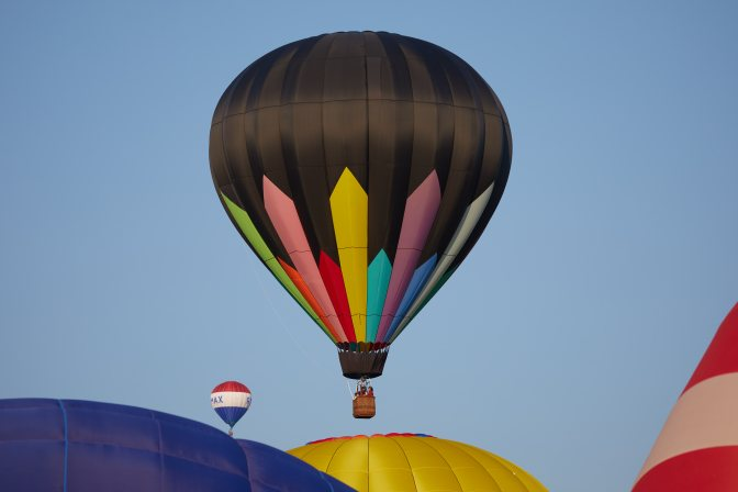 Multicolored balloon above three other balloons.
