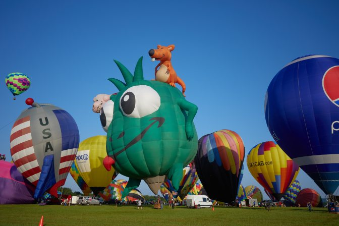 Balloons on ground, ready to take off, including one shaped as a green monster, and another shaped as a rocket ship with an American flag on it.