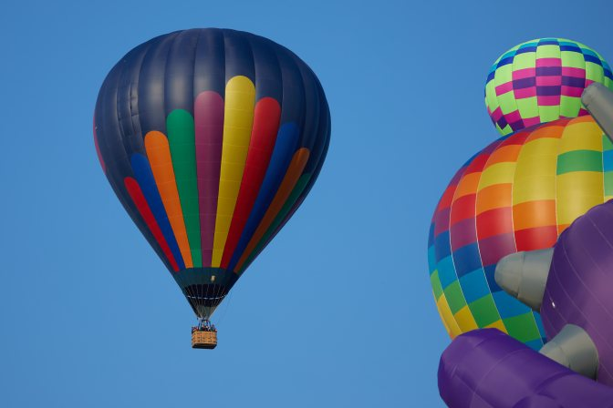 Multi-colored ballon in flight, moving past two balloons still on ground.
