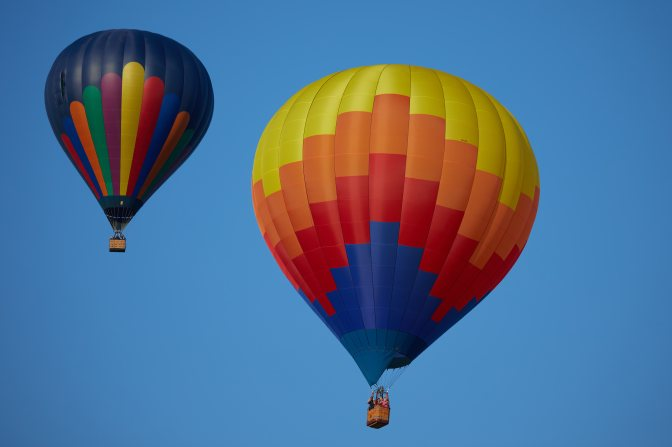 Two multi-colored balloons in sky.