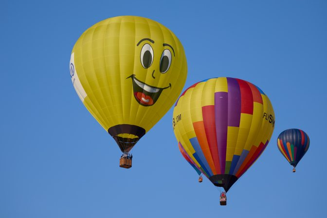 Two multicolored balloons, and yellow ballon with smiley face.