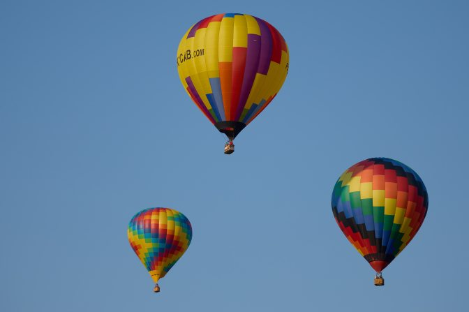 Three multicolored balloons in air.